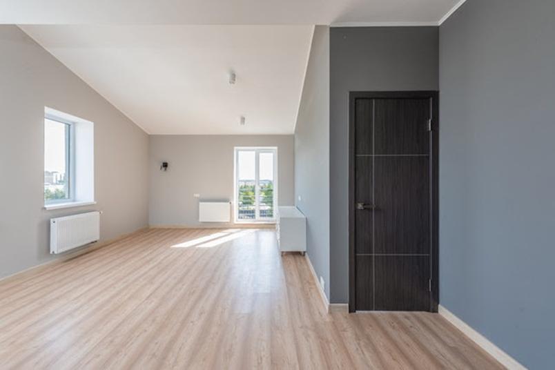 an empty room two windows and hardwood floor